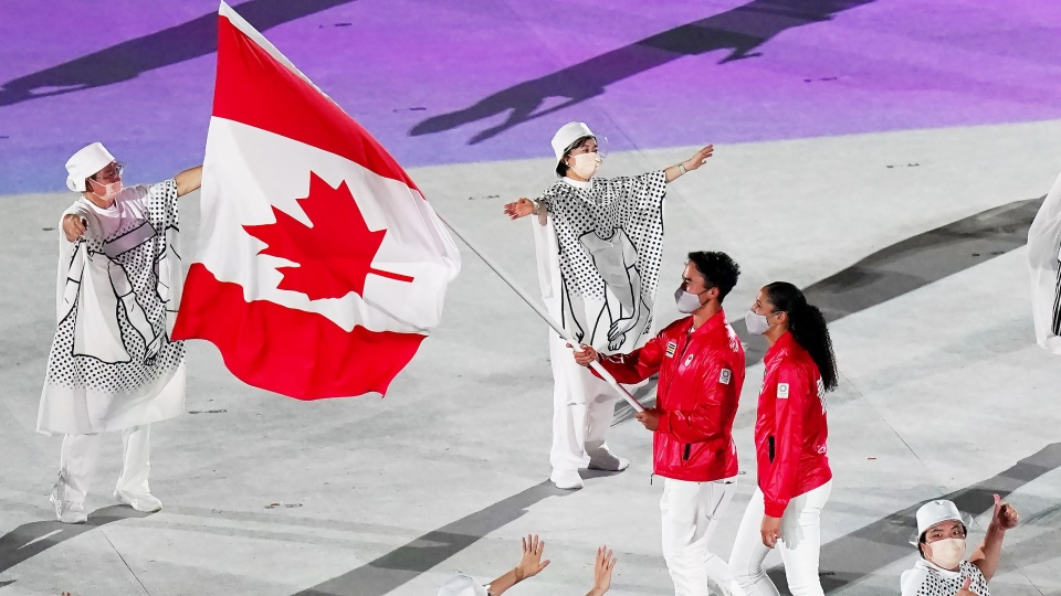 Team Canada flag-bearers Miranda Ayim and Nathan Hirayama carry the Canadian flag at the opening ceremonies during the Tokyo Olympics in Tokyo, Japan on Friday, July 23, 2021. THE CANADIAN PRESS/Nathan Denette