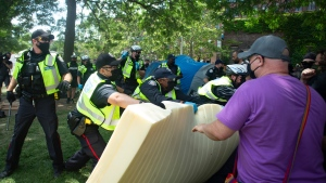 Toronto police grab a foam mattress that encampment supporters used as a barricade as police and city workers clear the Lamport Stadium Park homeless encampment in Toronto on Wednesday, July 21, 2021. THE CANADIAN PRESS/Chris Young