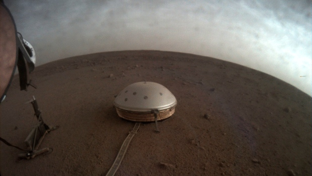 In this undated photo made available by NASA on Thursday, July 22, 2021, clouds drift over the dome-covered SEIS seismometer of the InSight lander on the surface of Mars. The quake-measuring device is providing the first detailed look at the red planet's interior, revealing a surprisingly thin crust and a molten core. In a series of articles published in July 2021, scientists reported that the Martian crust is within the thickness range of Earth's. (NASA/JPL-Caltech via AP)