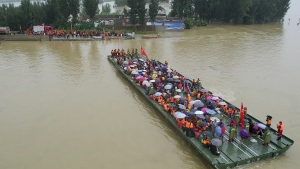 Rescuers use a motorized raft bridge to evacuate residents from a flooded rural area in Xinxiang in central China's Henan Province, Friday, July 23, 2021. The death toll from catastrophic flooding in the central Chinese city of Zhengzhou has continued to rise, state media reported Friday. The official China Daily newspaper and other media said the number included just Zhengzhou, the capital of Henan province. Other areas of the province have also faced heavy downpours, and rivers and reservoirs burst their banks. (Chinatopix via AP)
