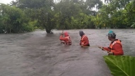 In this photo provided by the Philippine Coast Guard, members of the Philippine coastguard wade along floodwaters as they look for residents to be evacuated to safer grounds, in Naujan, Oriental Mindoro province, central Philippines on Friday July 23, 2021. Thousands of residents fled from flooded communities and swollen rivers in the Philippine capital and outlying provinces Saturday after days of torrential monsoon rains, which left at least one villager dead, officials said. (Philippine Coast Guard via AP)