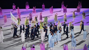 The refugee team carry the Olympic flag during the opening ceremony in the Olympic Stadium at the 2020 Summer Olympics, Friday, July 23, 2021, in Tokyo, Japan. (Dylan Martinez/Pool Photo via AP)