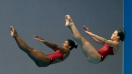 FILE - Jennifer Abel and Melissa Citrini-Beaulieu of Canada compete in the preliminary of the women's 3 meter synchronized springboard diving competition at the World Swimming Championships in Gwangju, South Korea, Monday, July 15, 2019. (AP Photo/Mark Schiefelbein)