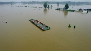 Rescuers ride a motorized raft bridge to evacuate residents from a flooded rural area in Xinxiang in central China's Henan Province, Friday, July 23, 2021. The death toll from catastrophic flooding in the central Chinese city of Zhengzhou has continued to rise, state media reported Friday. The official China Daily newspaper and other media said the number included just Zhengzhou, the capital of Henan province. Other areas of the province have also faced heavy downpours, and rivers and reservoirs burst their banks. (Chinatopix via AP)