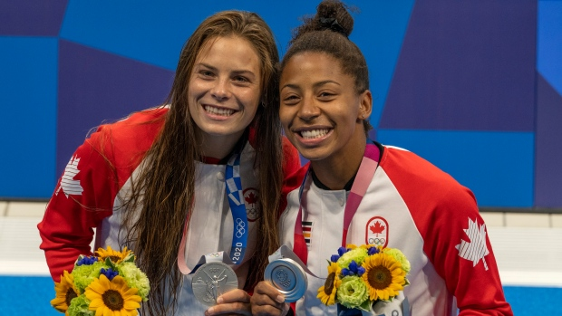 Canadian divers Jennifer Abel (Right) and Melissa Citrini-Beaulieu show off their medals after winning silver in the women's three-metre synchronized springboard diving during the Tokyo Olympics in Tokyo, Japan on Sunday, July 25, 2020. THE CANADIAN PRESS/ Frank Gunn