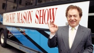 FILE - Actor/comedian Jackie Mason stands beside a bus displaying a sign advertising his TV show, 1992. Mason, a rabbi-turned-jokester whose feisty brand of standup comedy got laughs from nightclubs in the Catskills to West Coast talk shows and Broadway stages, has died. He was 93. Mason died Saturday, July 24, 2021, in Manhattan, the celebrity lawyer Raoul Felder told The Associated Press. (AP Photo/File)