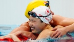 Canada's Margaret Mac Neil celebrates her gold medal swim in the women's 100m butterfly final with Sweden's Sarah Sjoestroem during the Tokyo Olympics in Tokyo, Japan on Monday, July 26, 2021. THE CANADIAN PRESS/Frank Gunn