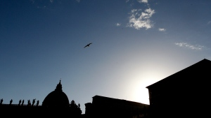 FILE - In this Thursday, June 29, 2017 file photo, St. Peter's Basilica is silhouetted at dusk, at the Vatican. Vatican prosecutors have alleged a jaw-dropping series of scandals in launching the biggest criminal trial in the Vatican's modern history, which opens Tuesday in a modified courtroom in the Vatican Museums. The once-powerful cardinal and nine other people are accused of bleeding the Holy See of tens of millions of dollars in donations through bad investments, deals with shady money managers and apparent favors to friends and family. (AP Photo/Riccardo De Luca, File)