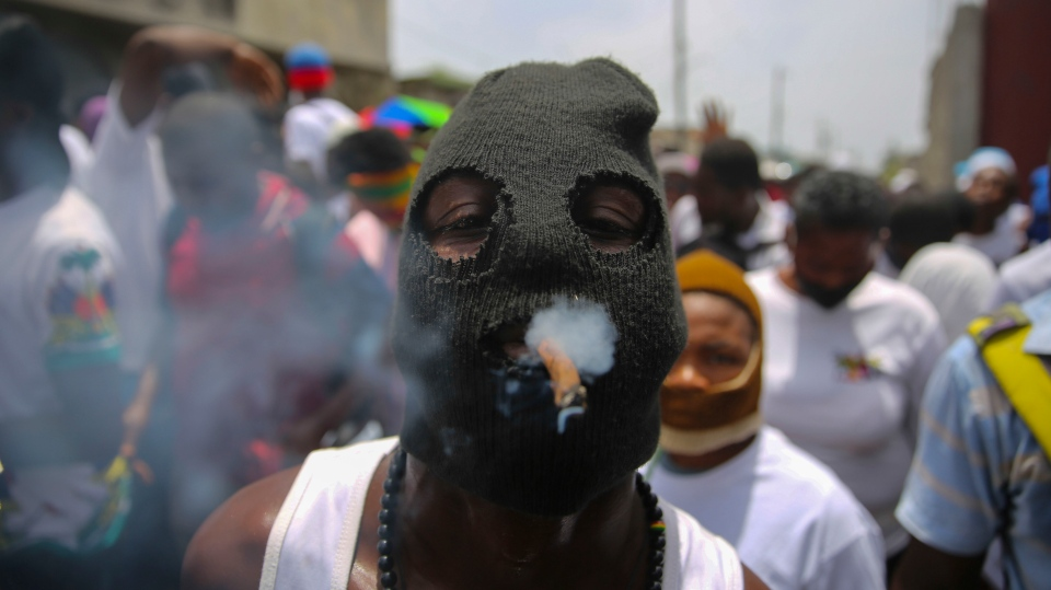 """A member of the gang led by Jimmy Cherizier, alias Barbecue, a former police officer who heads a gang coalition known as """"G9 Family and Allies, joins a march to demand justice for slain Haitian President Jovenel in Lower Delmas, a district of Port-au- Prince, Haiti Monday, July 26, 2021. Moise was assassinated on July 7 at his home. (AP Photo/Joseph Odelyn)"""