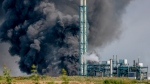 A dark cloud of smoke rises above the Chempark in Leverkusen, Germany, Tuesday, July 27, 2021. After an explosion, fire brigade, rescue forces and police are currently in large-scale operation, the police explained.(Oliver Berg/dpa via AP)