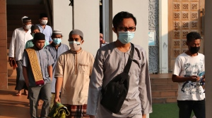 Muslims wearing face masks to curb the spread of coronavirus leave after an Eid al-Adha prayer at Zona Madina mosque in Bogor, Indonesia, Tuesday, July 20, 2021. Muslims across Indonesia marked a grim Eid al-Adha festival for a second year Tuesday as the country struggles to cope with a devastating new wave of coronavirus cases and the government has banned large gatherings and toughened travel restrictions. (AP Photo/Tatan Syuflana)