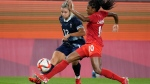 Britain's Rachel Daly, left, and Canada's Ashley Lawrence battle for the ball during a women's soccer match at the 2020 Summer Olympics, Tuesday, July 27, 2021, in Kashima, Japan. (AP Photo/Fernando Vergara)