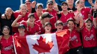 Canada's women's softball team pose for a photo with the Canadian flag after their win over Mexico in the bronze medal game at the Tokyo Olympics, Tuesday, July 27, 2021 in Yokohama, Japan. THE CANADIAN PRESS/Adrian Wyld