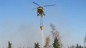 A helicopter drops water on the the Red Lake 65 Forest Fire in northern Ontario. (@ONforestfires /Twitter)