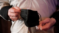 FILE - Sean Glass, a bartender at The Smiling Moose Bar/Restaurant, shows his COVID-19 protective covering he has at the ready Friday, May 14, 2021, in Pittsburgh's South Side neighborhood. (AP Photo/Keith Srakocic)