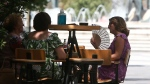 Women sit at a cafe on a hot day in downtown Skopje, North Macedonia, Wednesday July 28, 2021. Authorities in North Macedonia have issued a weather warning and recommended a set of measures on Wednesday as the tiny Balkan country is facing extreme high temperatures rising over 43 Celsius degrees (109 Fahrenheit). (AP Photo/Boris Grdanoski)