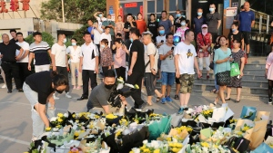 Bystanders watch as people place bouquets of flowers outside the entrance to a subway station in Zhengzhou in central China's Henan Province, Tuesday, July 27, 2021. Residents laid bouquet after bouquet, the neatly tied yellow and white flowers standing on end, on Tuesday outside an entrance to a subway station in central China where more than a dozen people died last week after a record-breaking downpour flooded large swaths of Henan province. (Chinatopix via AP)