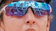 Melissa Humana-Paredes, of Canada, competes during a women's beach volleyball match against Switzerland as her sunglasses reflect the beach volleyball court at the 2020 Summer Olympics, Thursday, July 29, 2021, in Tokyo, Japan. (AP Photo/Petros Giannakouris)
