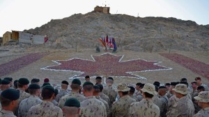 Canadian soldiers gather at the base of a rock memorial to fallen Canadian soldiers at a forward operating base in Panjwaii district. Memorial stones signifying the deaths of 72 soldiers were buried in a sunset ceremony in Ma'sum Ghar, Afghanistan on Wednesday, June 8, 2011. THE CANADIAN PRESS/Murray Brewster
