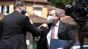 Italy's Prime Minister Mario Draghi, right, elbow bumps European Commissioner for An Economy that Works for People Valdis Dombrovskis as he arrives for an EU summit at the Alfandega do Porto Congress Center in Porto, Portugal, Friday, May 7, 2021. (Jose Coelho, Pool via AP)