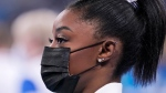 Simone Biles, of the United States, wears a face mask and waits for her turn to perform during the artistic women's team final at the 2020 Summer Olympics, Tuesday, July 27, 2021, in Tokyo. (AP Photo/Gregory Bull)