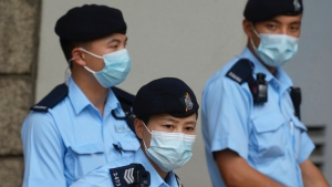 Police officers stand guard outside a court Friday, July 30, 2021 in Hong Kong. (AP Photo/Vincent Yu)