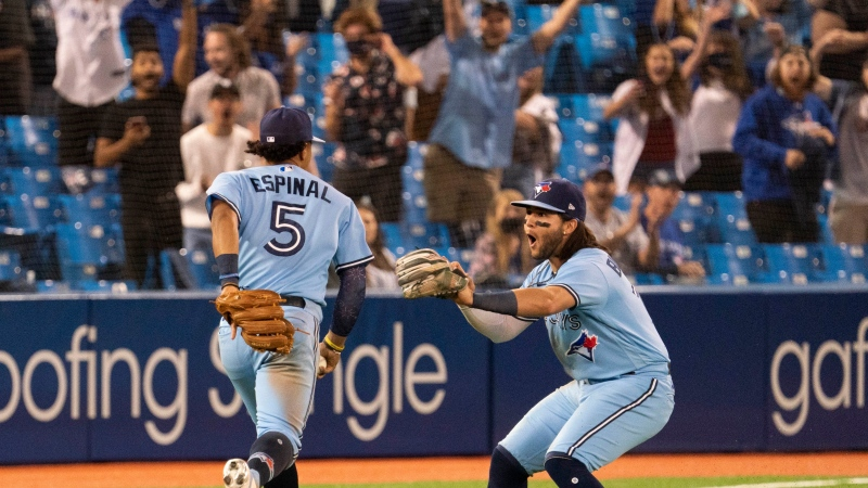 Toronto Blue Jays shortstop Bo Bichette (11) reacts as Blue Jays third baseman Santiago Espinal (5) makes a bare-handed catch to end the game against the Kansas City Royals in the ninth inning of MLB action in Toronto on Friday, July 30, 2021. THE CANADIAN PRESS/Peter Power