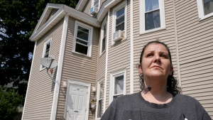 Roxanne Schaefer, of West Warwick, R.I., stands for a photograph outside of her apartment building, in West Warwick, Tuesday, July 27, 2021. Schaefer, who is months behind on rent, is bracing for the end to a CDC federal moratorium Saturday, July 31, 2021, a move that could result in millions of people being evicted just as the highly contagious delta variant of the coronavirus is rapidly spreading. (AP Photo/Steven Senne)