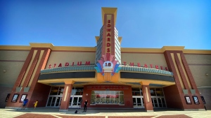 """News crews report from in front of the Regal Edwards Corona Crossings movie theater, Tuesday, July 27, 2021, in Corona, Calif., following a shooting at the theater the night before that killed an 18-year-old woman and seriously wounded a 19-year-old social media influencer as they watched """"The Forever Purge."""" (Terry Pierson/The Orange County Register via AP)"""