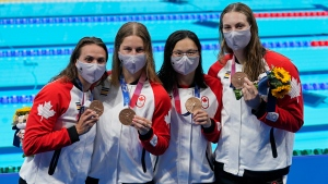 Canada's Kylie Masse, left to right, Sydney Pickrem, Maggie Mac Neil and Penny Oleksiak celebrate a bronze medal in the women's 4 x 100m medley relay final during the Tokyo Summer Olympic Games, in Tokyo, Sunday, August 1, 2021. THE CANADIAN PRESS/Adrian Wyld