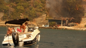 People use a boat to evacuate from smoke-engulfed Mazi area with a burning house and a car in the background, in Bodrum, Mugla, Turkey, Sunday, Aug. 1, 2021. Wildfires raged Sunday near Turkey's holiday beach destinations of Antalya and Mugla as the discovery of more bodies caused the death toll to rise to eight. Residents and tourists fled the danger in small boats while the coast guard and two navy ships waited out at sea in case a bigger evacuation was needed. (IHA via AP)