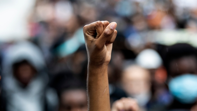 A protester holds up a fist as demonstrators gather in Toronto to honour black lives lost at the hands of police, on Friday, June 5, 2020. THE CANADIAN PRESS/Chris Young