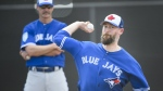 Toronto Blue Jays pitcher John Axford, right, throws a bullpen session as Blue Jays pitching coach Pete Walker looks on during baseball spring training in Dunedin, Fla., on Wednesday, February 20, 2019. The Toronto Blue Jays have re-signed Canadian reliever John Axford to a minor-league deal. THE CANADIAN PRESS/Nathan Denette