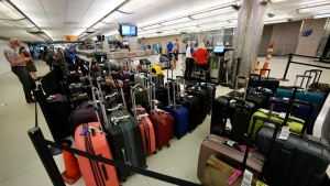 Baggage stacks up from delayed travellers in the baggage claim area in Denver International Airport Wednesday, June 16, 2021, in Denver. (AP Photo/David Zalubowski)