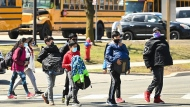 Students cross the street at Tomken Road Middle School as Ontario prepares for its third province wide lockdown during the COVID-19 pandemic in Mississauga, Ont., on Thursday, April 1, 2021. THE CANADIAN PRESS/Nathan Denette