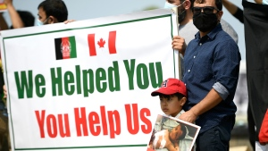 People participate in a rally calling on the Canadian government to evacuate the families of interpreters and locally employed civilians who supported the Canadian Armed Forces in Afghanistan as they are being targeted by the Taliban, on Parliament Hill in Ottawa, on Tuesday, Aug. 3, 2021. THE CANADIAN PRESS/Justin Tang