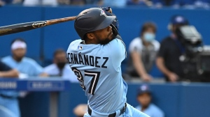 Toronto Blue Jays' Teoscar Hernandez hits a two run home run, scoring Bo Bichette in the first inning of a baseball game against the Cleveland Indians, in Toronto on Tuesday, August 3, 2021. THE CANADIAN PRESS/Jon Blacker