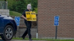 An election worker carries a sign at a voting place for the New Brunswick provincial election in Quispamsis, N.B., Monday, Sept. 14, 2020. THE CANADIAN PRESS/Andrew Vaughan