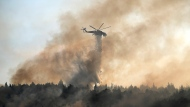 A helicopter drops water over a fire in Varibobi area, northern Athens, Greece, Wednesday, Aug. 4, 2021. Firefighting planes were resuming operation at first light Wednesday to tackle a major forest fire on the northern outskirts of Athens which raced into residential areas the previous day, forcing thousands to flee their homes amid Greece's worst heatwave in decades. (AP Photo/Thanassis Stavrakis)
