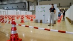 An official stands at attention inside a COVID-19 testing site in the Main Press Center at the 2020 Summer Olympics, Thursday, July 22, 2021, in Tokyo, Japan. (AP Photo/John Minchillo)