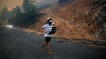 A man runs away from the blaze approaching in the background, in Milas, Mugla, Turkey, Tuesday, Aug. 3, 2021. As Turkish fire crews pressed ahead Tuesday with their weeklong battle against blazes tearing through forests and villages on the country's southern coast, President Recep Tayyip Erdogan's government faced increased criticism over its apparent poor response and inadequate preparedness for large-scale wildfires. Fed by strong winds and scorching temperatures, the fires that began Wednesday have left eight people dead, forced thousands of residents and tourists to flee homes or vacation resorts in boats or convoys of cars and trucks.(AP Photo/Emre Tazegul)