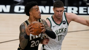 Atlanta Hawks' John Collins (20) drives the ball to the basket against Milwaukee Bucks' Brook Lopez (11) during the first half of Game 4 of the NBA basketball Eastern Conference finals Tuesday, June 29, 2021, in Atlanta. (AP Photo/Brynn Anderson)