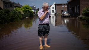 In this Saturday, July 17, 2021 file photo, Wiel de Bie, 75, stands outside his flooded home in the town of Brommelen, Netherlands. Scientists say there's something different this year from the recent drumbeat of climate weirdness. This summer a lot of the places hit by weather disasters are not used to getting extremes and many of them are wealthier, which is different from the normal climate change victims. That includes unprecedented deadly flooding in Germany and Belgium, 116-degree heat records in Portland, Oregon and similar blistering temperatures in Canada, along with wildfires. Now Southern Europe is seeing scorching temperatures and out-of-control blazes too. And the summer of extremes is only getting started. Peak Atlantic hurricane and wildfire seasons in the United States are knocking at the door. (AP Photo/Bram Janssen, File)