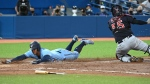 Toronto Blue Jays' George Springer, left, slides safely into home ahead of the tag by Cleveland Indians catcher Roberto Perez during fifth inning AL action Tuesday, August 3, 2021. THE CANADIAN PRESS/Jon Blacker