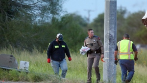 Texas Department of Public Safety pick up debris near a vehicle where multiple people died after the van carrying migrants tipped over just south of the Brooks County community of Encino on Wednesday, Aug. 4, 2021, in Encino, Texas. The van crashed against a utility pole after it attempted to turn off of Highway 281 onto Business 281. Encino is about 2 miles (3.22 kilometers) south of the Falfurrias Border Patrol checkpoint. (Delcia Lopez/The Monitor via AP)