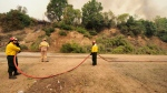 Firefighters hold a water hose during a wildfire near Kechries village on the island of Evia, about 144 kilometers (90 miles) north of Athens, Greece, Thursday, Aug. 5, 2021. Forest fires fueled by a protracted heat wave raged overnight and into Thursday in Greece, threatening the archaeological site at the birthplace of the modern Olympics and forcing the evacuation of dozens of villages. (AP Photo/Thodoris Nikolaou)