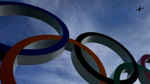 A passenger jet flies over the Olympic rings on display outside the Olympic Stadium where the athletic events are underway at the 2020 Summer Olympics Thursday, Aug. 5, 2021, in Tokyo, Japan. (AP Photo/Charlie Riedel)