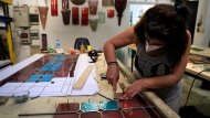 A stain glass artist works to recreate one of the stained-glass windows that were the trademark of Beirut's Sursock Museum, shattered in last year's port explosion, at the Maya Hussaini workshop, in Beirut, Lebanon, Monday, June 28, 2021. Lebanon's only modern art museum, the Sursock, was the beating heart of Beirut's arts community, and some hope that reopening it will be a first step in the harder task of  rebuilding the city's once thriving arts scene. (AP Photo/Hussein Malla)