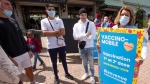 A healthcare worker talks to some young men about getting a first or second dose at a COVID-19 vaccination clinic at LaRonde amusement park Friday, July 30, 2021 in Montreal. The Quebec government is increasing its efforts to get more young people vaccinated. THE CANADIAN PRESS/Ryan Remiorz