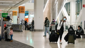 Travelers walk through the arrivals area at LaGuardia Airport Tuesday, Feb. 2, 2021, in New York.  (AP Photo/Frank Franklin II)